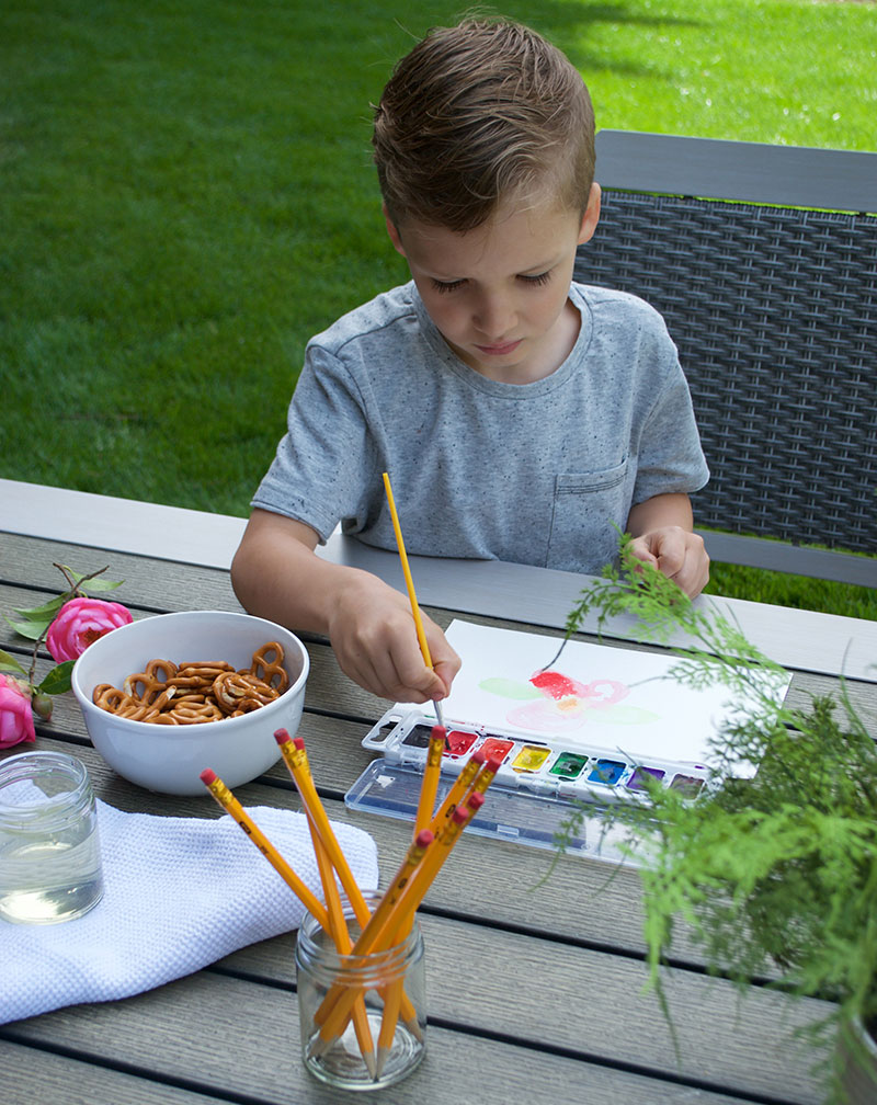detail of boy painting a picture outdoors on patio table