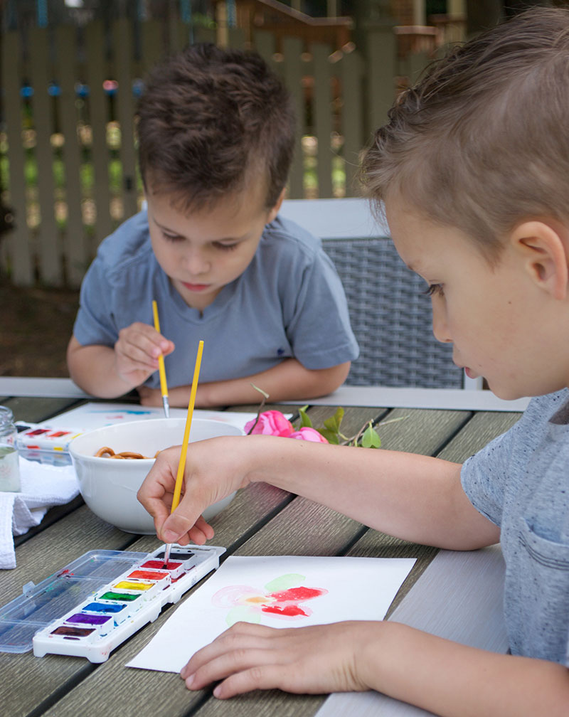 detail of two boys painting outside on patio table