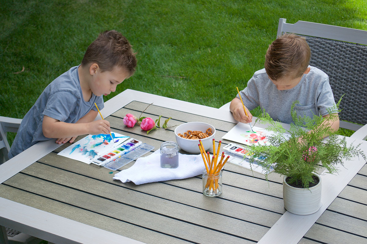 two boys painting on a patio table outdoors