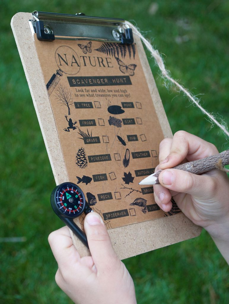 detail of nature scavenger hunt on clipboard with compass