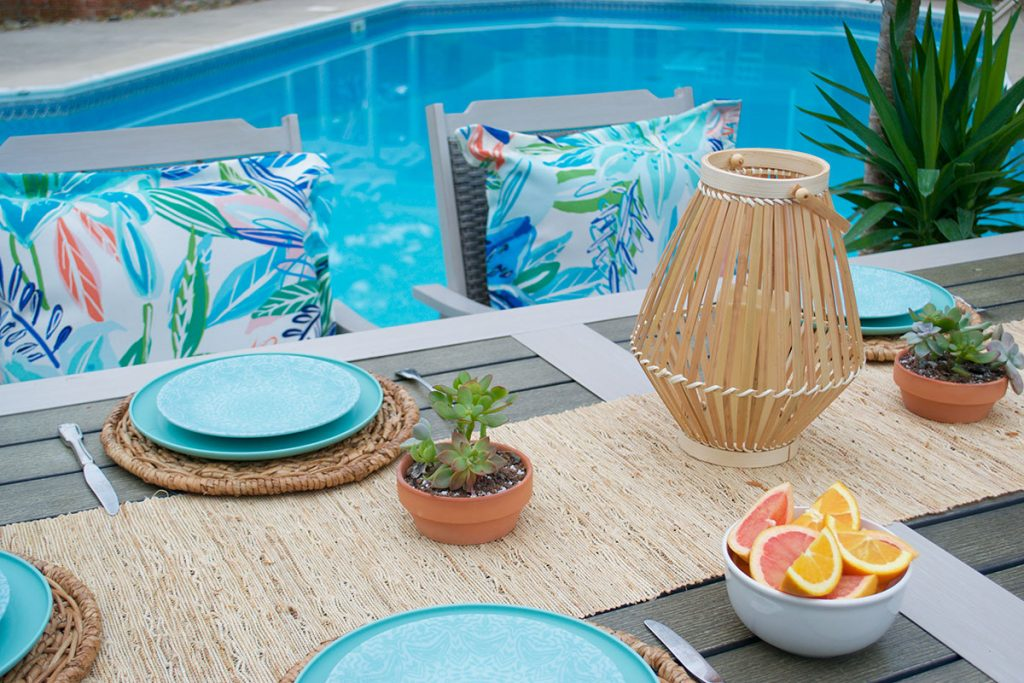 outdoor patio table with bright blue plates and colorful seat cushions