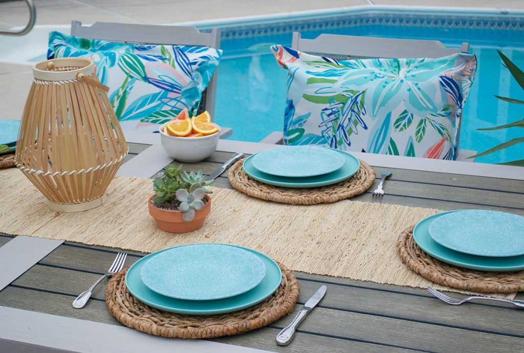 outdoor patio furniture set with summer colors on seat pillows and table settings