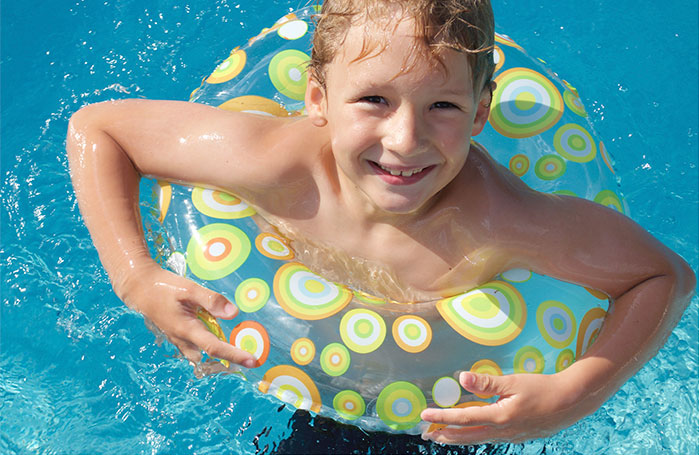 boy floating in swimming pool
