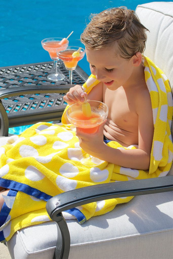 boy sitting in patio chair with popsicle drink