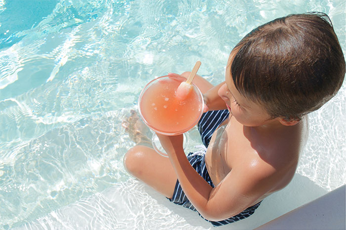 boy in pool with popsicle drink