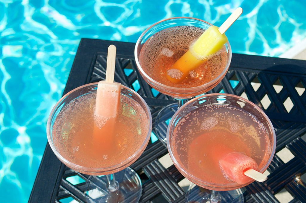 popsicle drinks on patio table in front of swimming pool