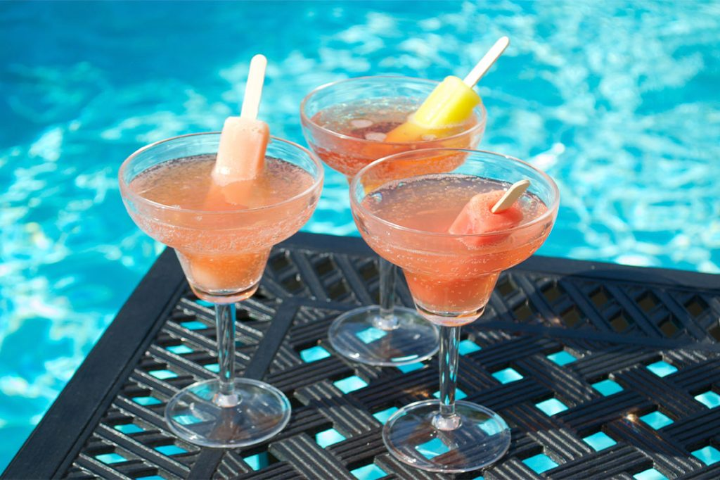 summer popsicle drinks on a patio tabel near swimming pool