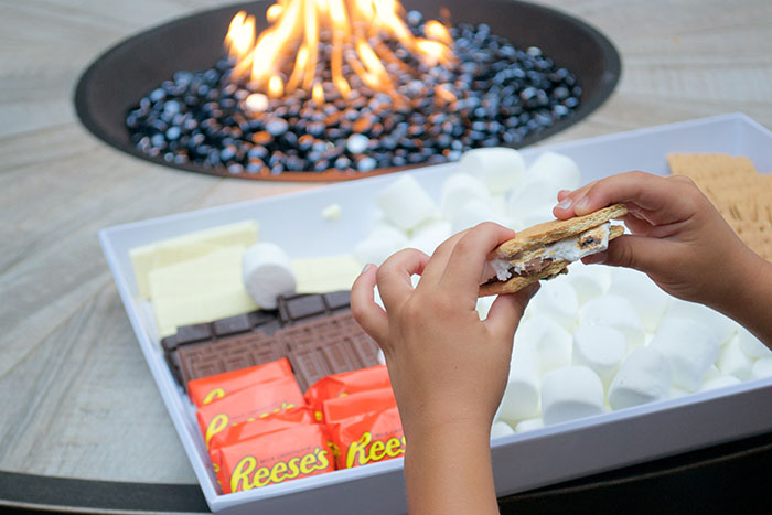 child holding smores near patio firepit