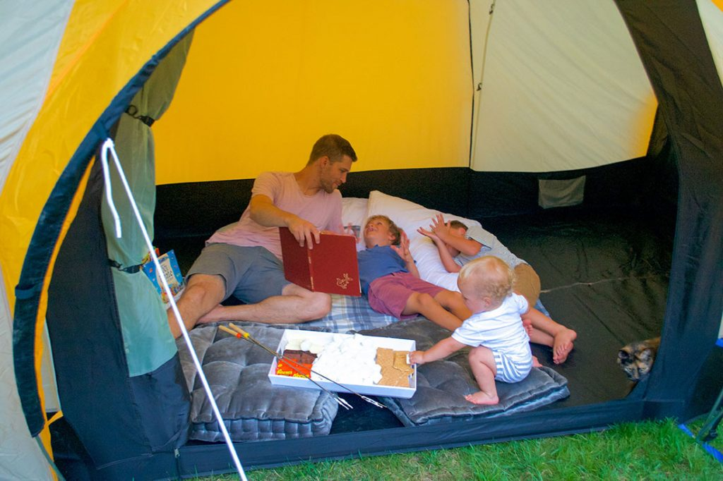 father reading with kids in backyard tent