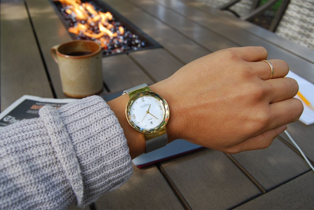 checking watch at outdoor table with firepit
