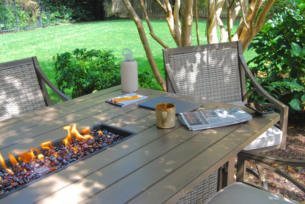 outdoor patio table with firepit and laptop