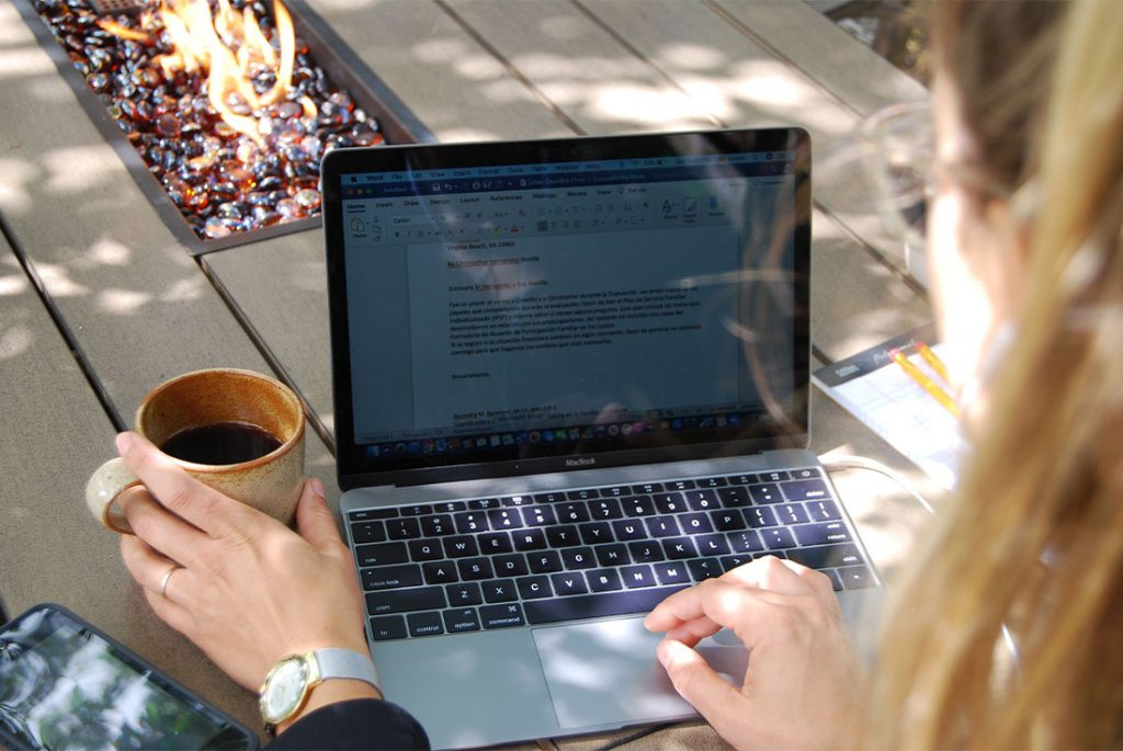 woman at outdoor table with laptop and coffee