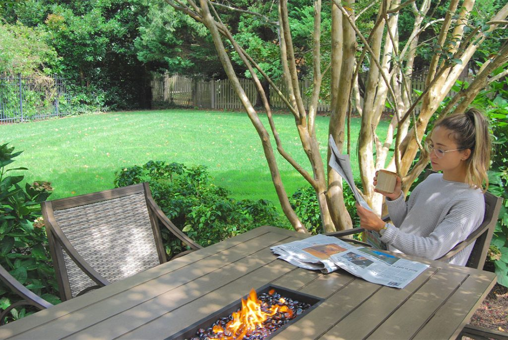woman reading paper at outdoor table with firepit