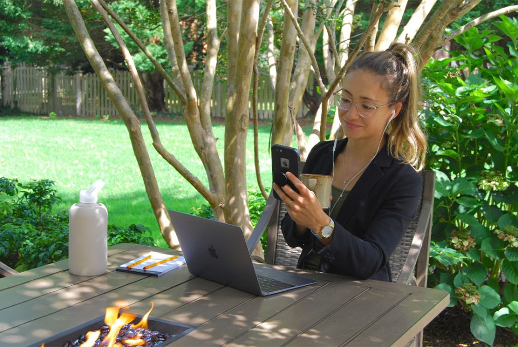 woman looking at phone sitting at outdoor table