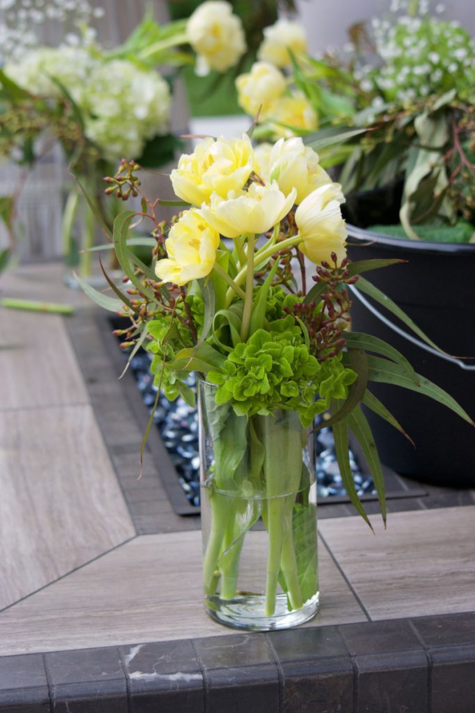 yellow flowers in vase on firepit table