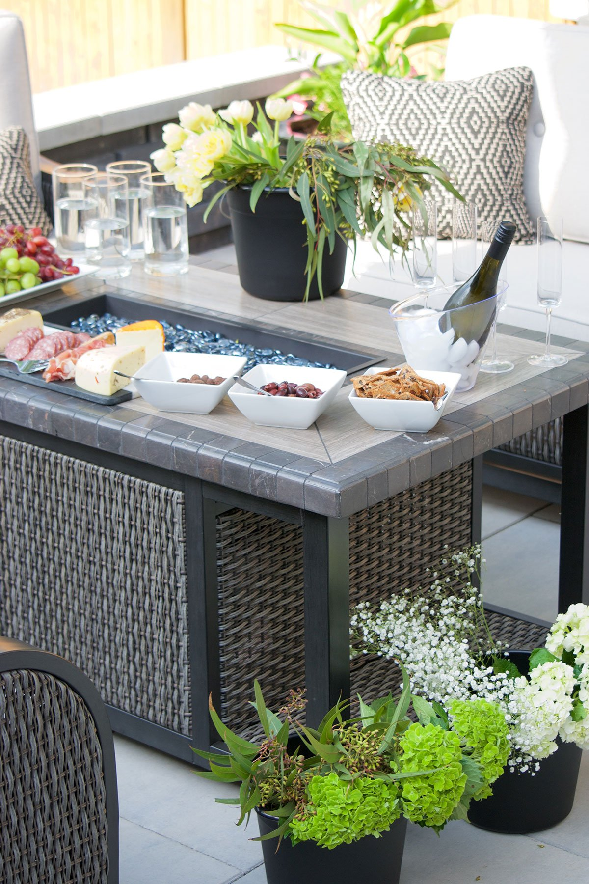 firepit table with party food and drinks and various flower arrangements