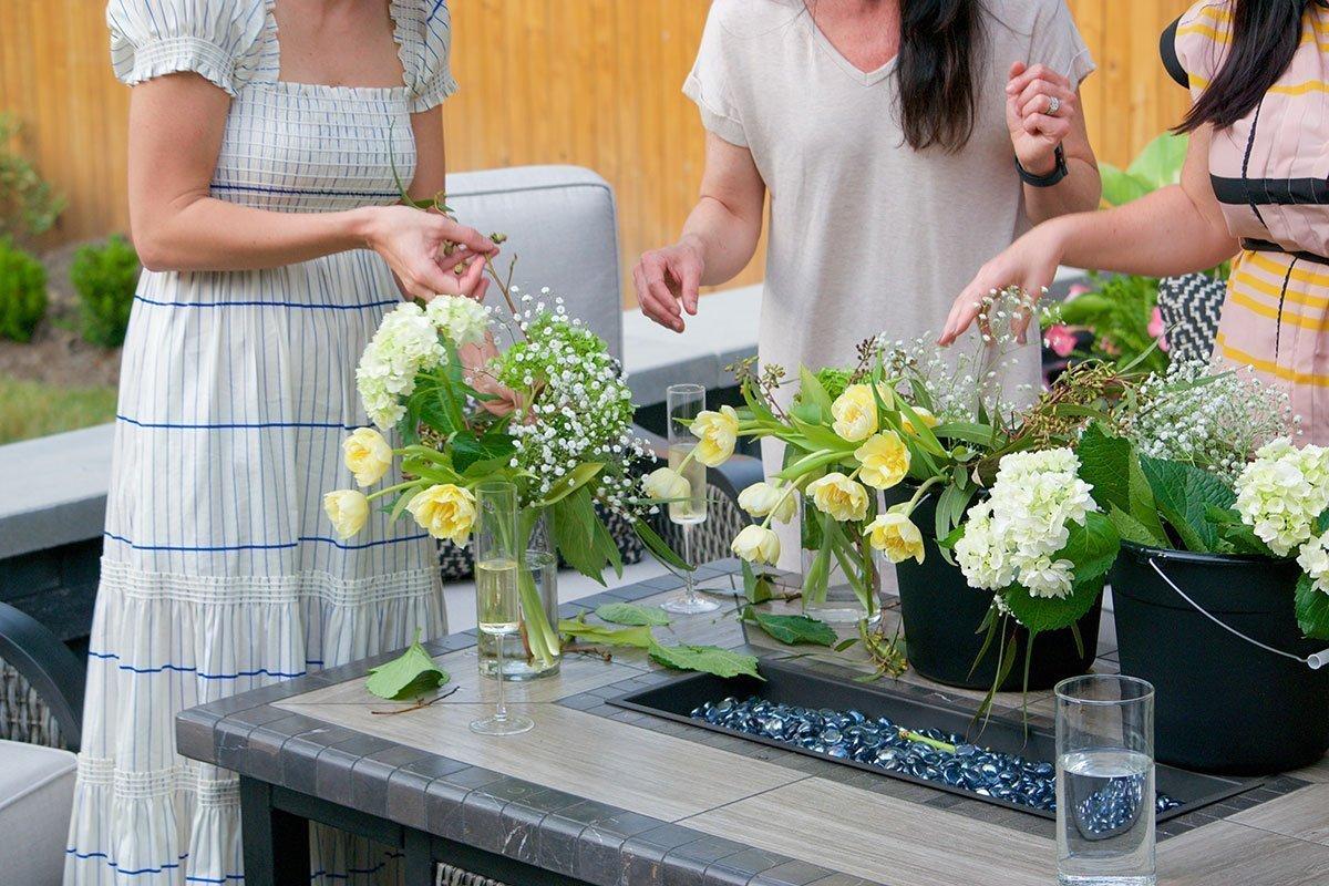 friends viewing flower arrangements on outdoor firepit table