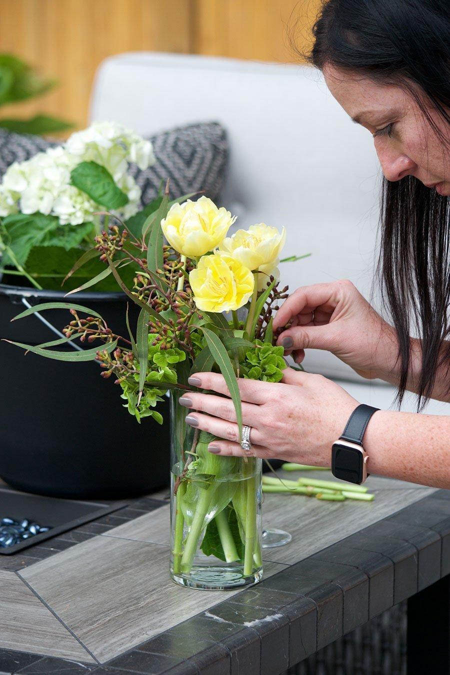 woman working on yellow flower arrangement