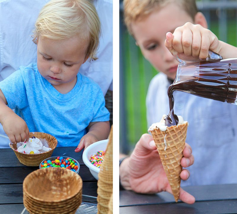 younger brother eating sundae while older brother pours hot fudge on an icecream cone