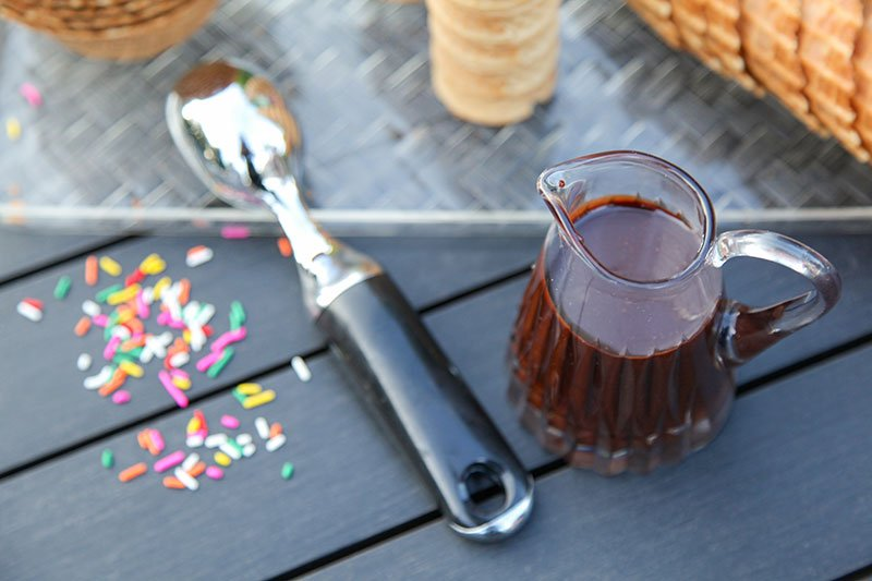 hot fudge pitcher, icecream scoop and sprinkles on patio table