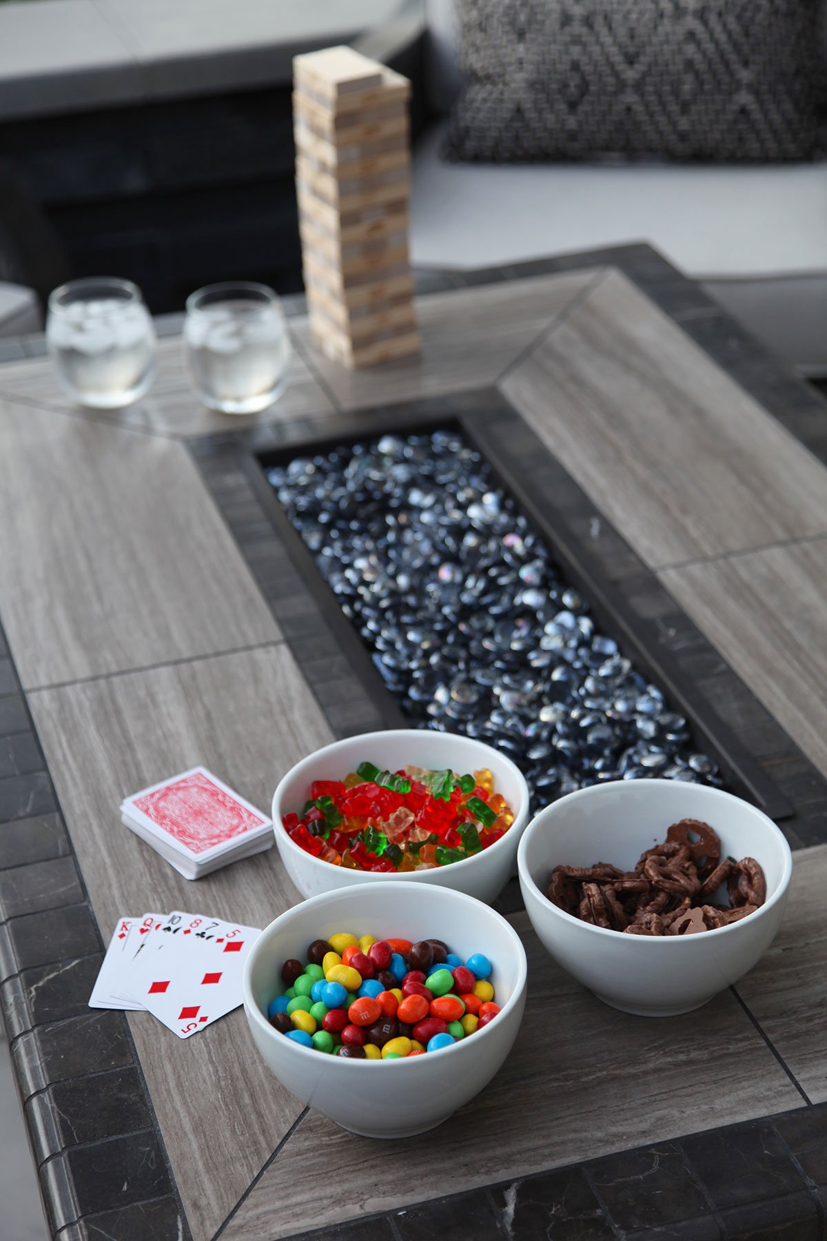 game, cards, goodies on outdoor fire pit table