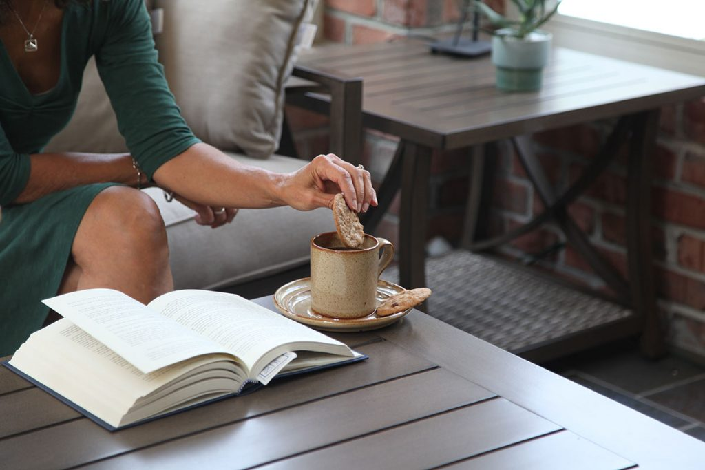 woman dipping cookie in tea on patio table