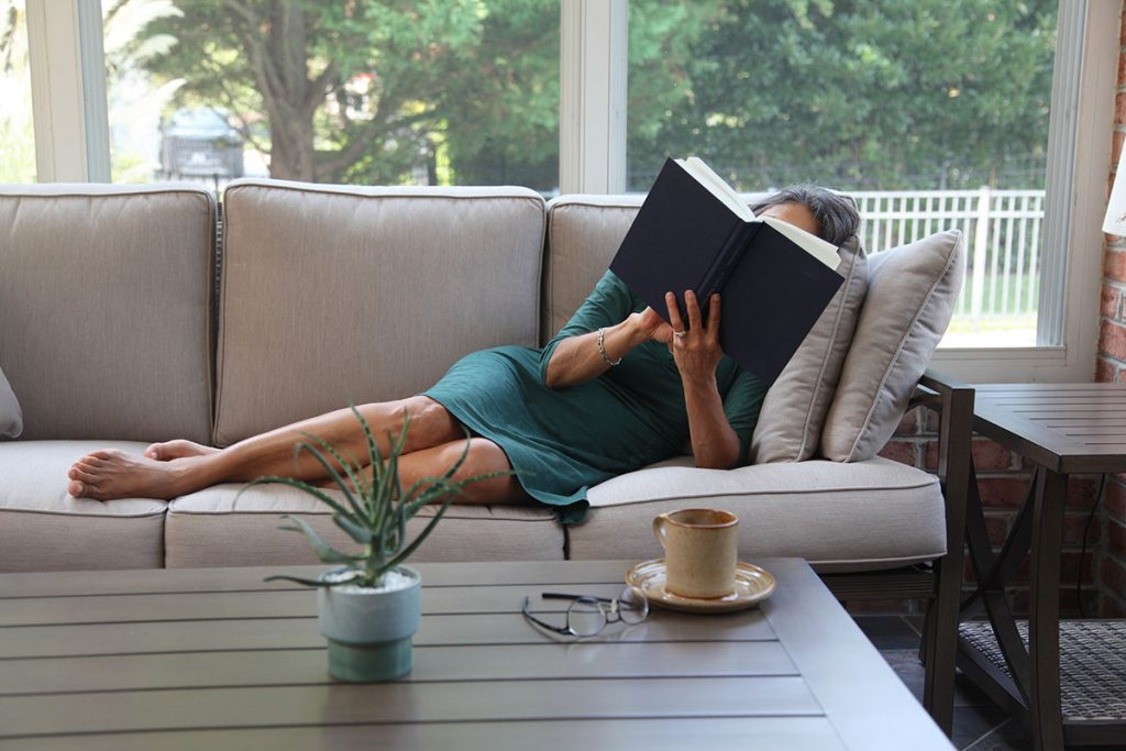 woman laying on patio couch reading book